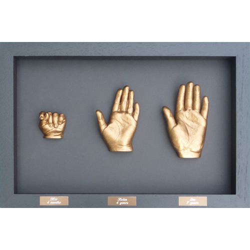Contemporary 16x10 black frame with gold casts of siblings aged 6 months, 4 and 7